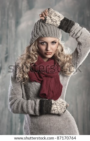 pretty young girl with curly blond hair in winter dress with hat and scarf playing and smiling to the camera - stock photo