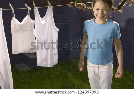 Pretty young girl with her pigtails flying standing in front of a washline with clean white washing - stock photo