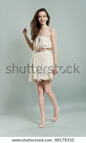 Pretty young girl with long hair over grey background - stock photo