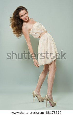 Pretty young girl with long hair over grey background