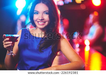Pretty young girl with martini looking at camera by the bar counter - stock photo