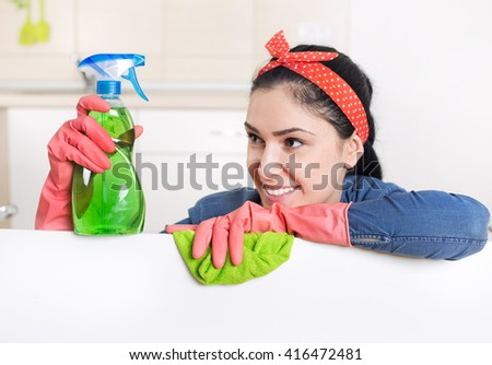 Pretty young girl with spray bottle and cloth behind blank white board - stock photo