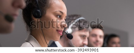 Pretty young girl working in call center business. Carefully listening to the client on phone - stock photo