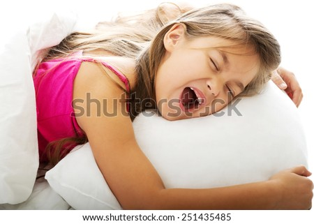 Pretty young girl yawning while waking up - stock photo