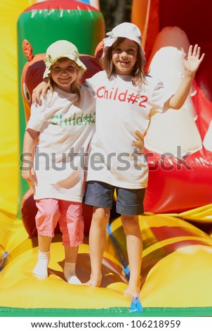 Pretty young girls posing in a bouncing castle in a bright sunny day with beautiful smile - stock photo