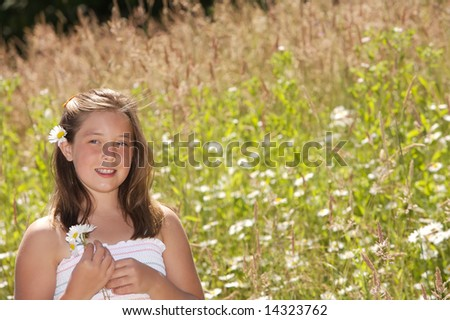 Pretty young girls standing in a field of daisies - stock photo