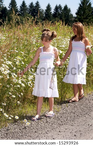 Pretty young girls walking by a field of daisies - stock photo