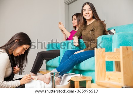 Pretty young Hispanic brunette relaxing at a nail salon while getting a pedicure - stock photo