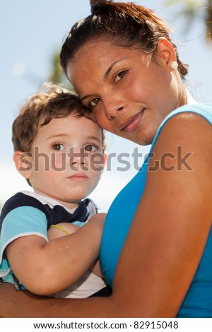 Pretty young hispanic woman with a cute young boy in an affectionate embrace outdoors in a park setting. - stock photo