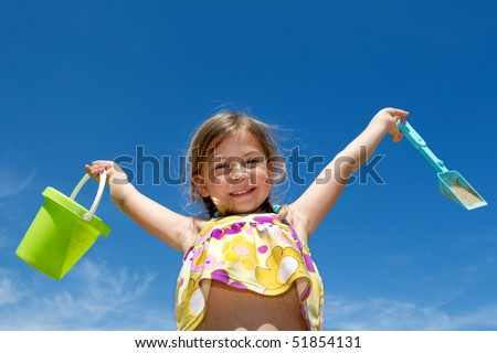 Pretty young holding her bucket and spade in the air on the beach - stock photo