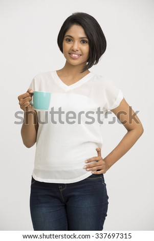 Pretty young Indian girl with coffee cup on white background. - stock photo