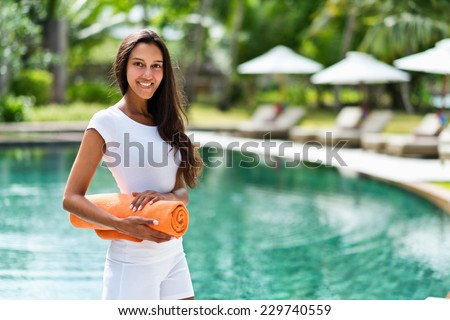 Pretty young Indian woman at a tropical resort standing in front of a sparkling pool with beach umbrellas with a rolled orange towel under her arm smiling at the camera - stock photo