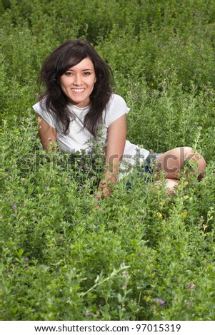 pretty young lady in white t-shirt and denim shorts resting on a grassy meadow hill