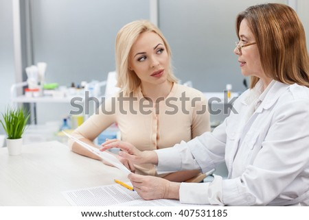 Pretty young lady is visiting general practitioner - stock photo