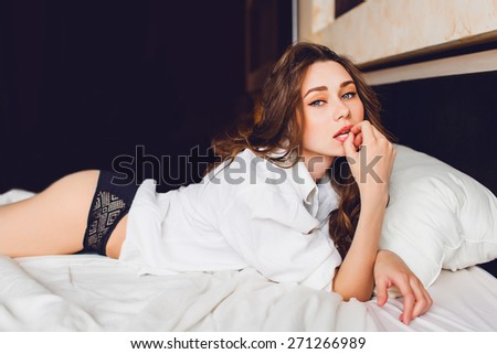 Pretty young lady just woke up in the early morning in her bedroom . Wearing sexy luxury stylish black lingerie and white short . Woman lying on her stomach on white bed. - stock photo