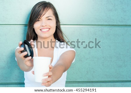 Pretty young lady smiling offering fresh coffee from takeaway mug outside on green wall with copy text area - stock photo