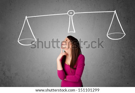 Pretty young lady taking a decision with scale above her head - stock photo