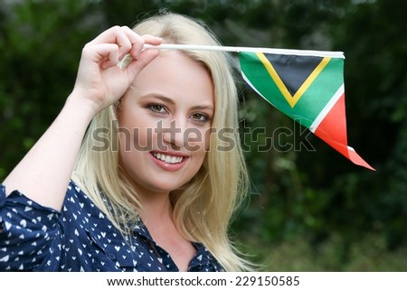 Pretty young lady waving the South African flag - stock photo