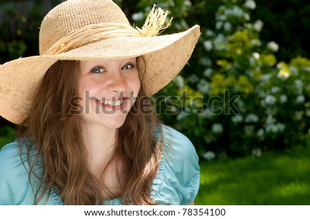 Pretty Young Lady Wearing a Hat in the Sunshine - stock photo
