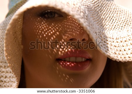 Pretty young lady with large hat at sunny day