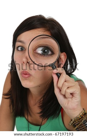 Pretty young lady with surprised  expression looking through a magnifying glass - stock photo