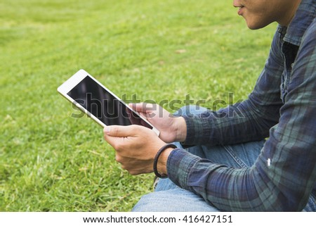 Pretty young man is using a Tablet PC