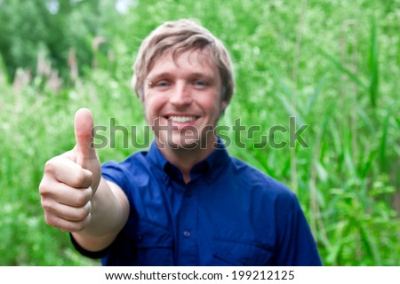 pretty young man smiling and showing thumbs up - stock photo
