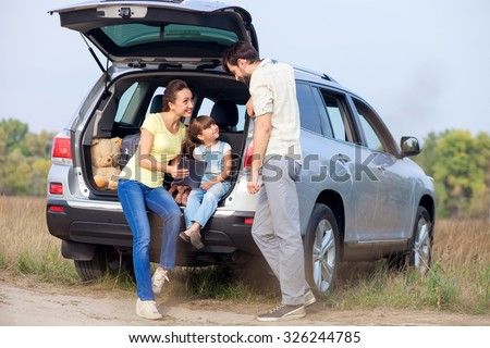 Pretty young married couple and their daughter are resting in the nature. The woman and girl are sitting on open car boot and using tablet. The man is standing near them. They are smiling