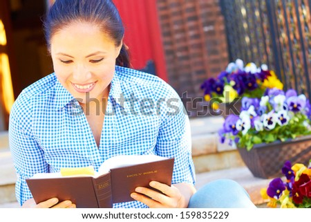 Pretty young mixed race woman in casual wear reading holy bible. - stock photo