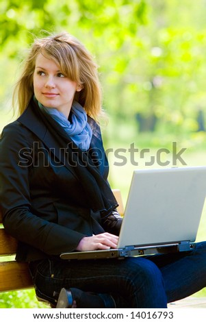 Pretty young model with laptop at park