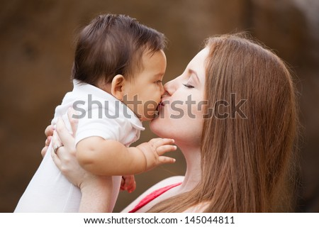 Pretty young Mom kissing her baby boy - stock photo