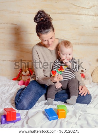 Pretty Young Mom with her Adorable Baby Boy Playing with Plastic Toys, Smiling at the Camera - stock photo