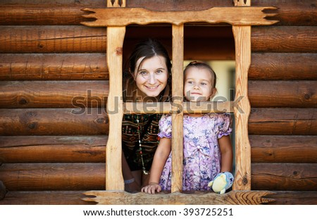 Pretty young mother and daughter a little girl look out of the window a wooden hut. Happy smiling mother and daughter. - stock photo