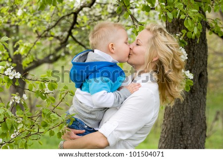 Pretty young mother getting a huge kiss from her baby son. - stock photo