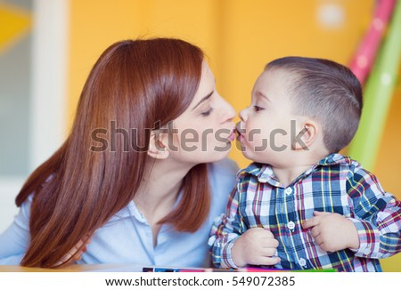 Pretty young mother kiss her baby son at home