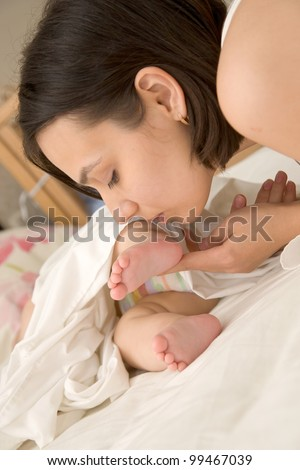 Pretty young mother kissing the tiny feet of her newborn baby who is sleeping in bed - stock photo