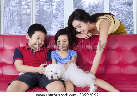 Pretty young mother playing a dog with her children on the sofa at home, shot with winter background on the window - stock photo
