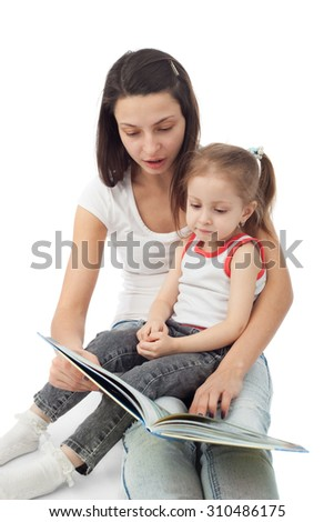 pretty young mother reading for her cute little daughter - stock photo