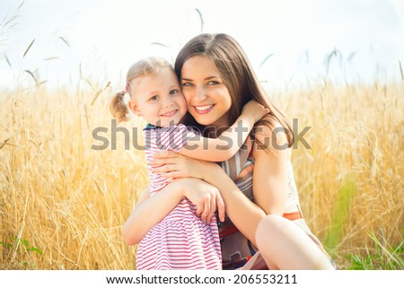 Pretty young mother with cute little daughter are happy in sunny day - stock photo