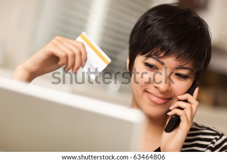Pretty Young Multiethnic Woman Holding Phone and Credit Card Using Laptop. - stock photo