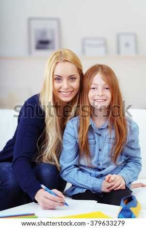 Pretty young Mum and her cute little daughter sitting on the sofa at home doing homework together for school - stock photo