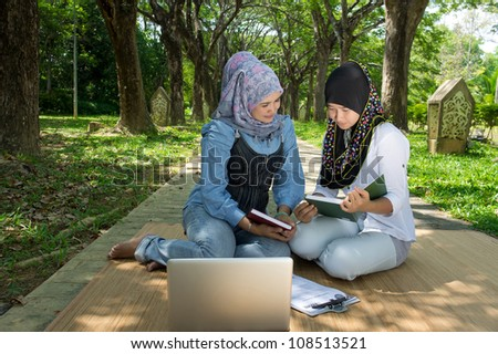 pretty young muslim girl studying with her mother at park - stock photo