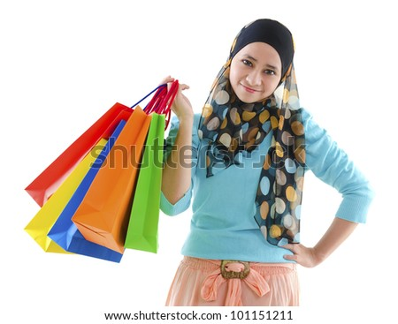 Pretty young muslim woman holding shopping bags - stock photo