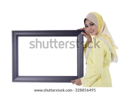Pretty young Muslim woman pose with holding a frame for text space - stock photo