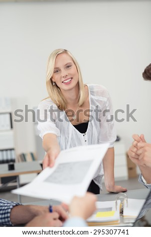 Pretty Young Office Woman Smiling at the Camera While Handing Over a Document to her Co-Worker at the Boardroom Table. - stock photo