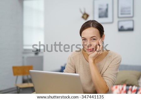 Pretty Young Office Woman with Laptop Smiling at the Camera While Leaning her Face on her Hand. - stock photo