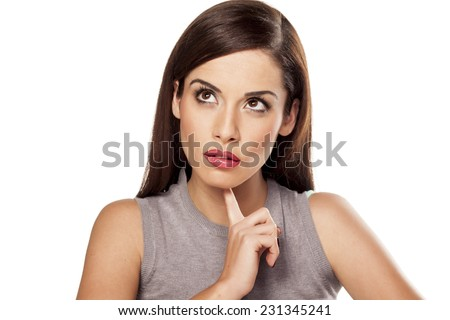 pretty young pensive woman touching her chin - stock photo