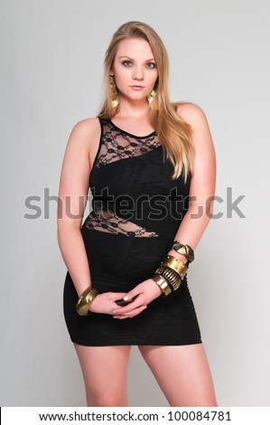 Pretty young plus size blonde in a black dress - stock photo