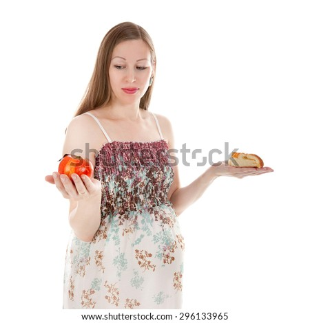 pretty young pregnant woman making her choice between cake and apple - stock photo