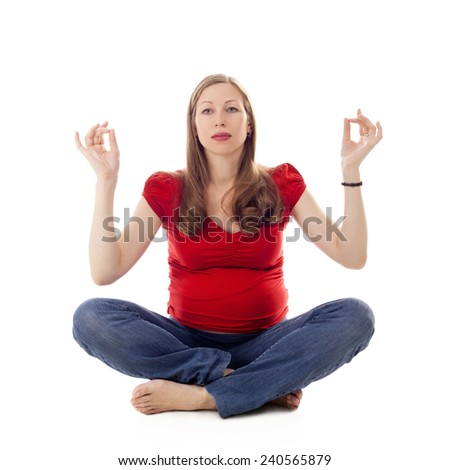 pretty young pregnant woman practicing yoga in studio